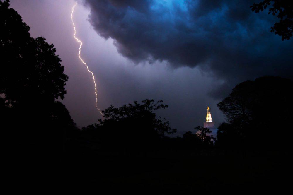 Lightening at night over the stupa of the temple Ruwanwelisaya with big blue storm cloud, Anuradhapura, Sri Lanka