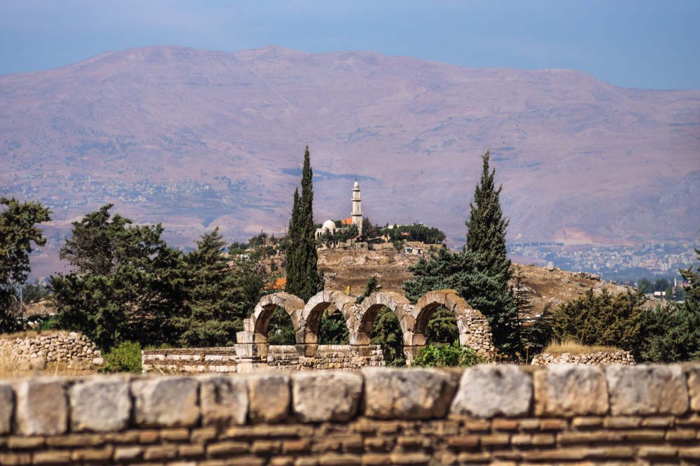 Mosque on a hill with purple blue coloured mountains in the background on a sunny day at Anjar ruins with walls and arches, Bekaa valley, Lebanon