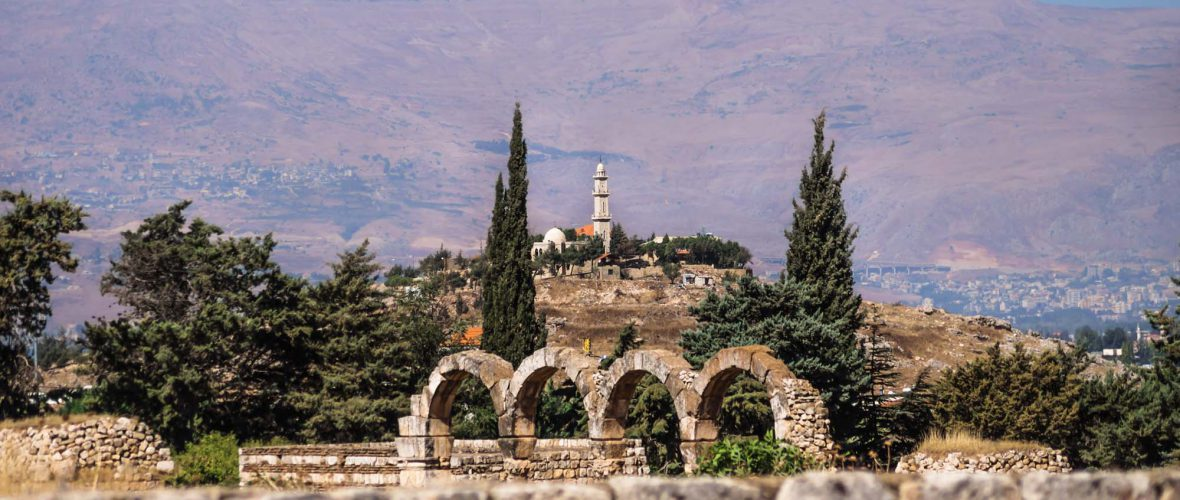 Bekaa valley, Lebanon, Mosque on a hill with purple blue coloured mountains in the background on a sunny day at Anjar ruins with walls and arches