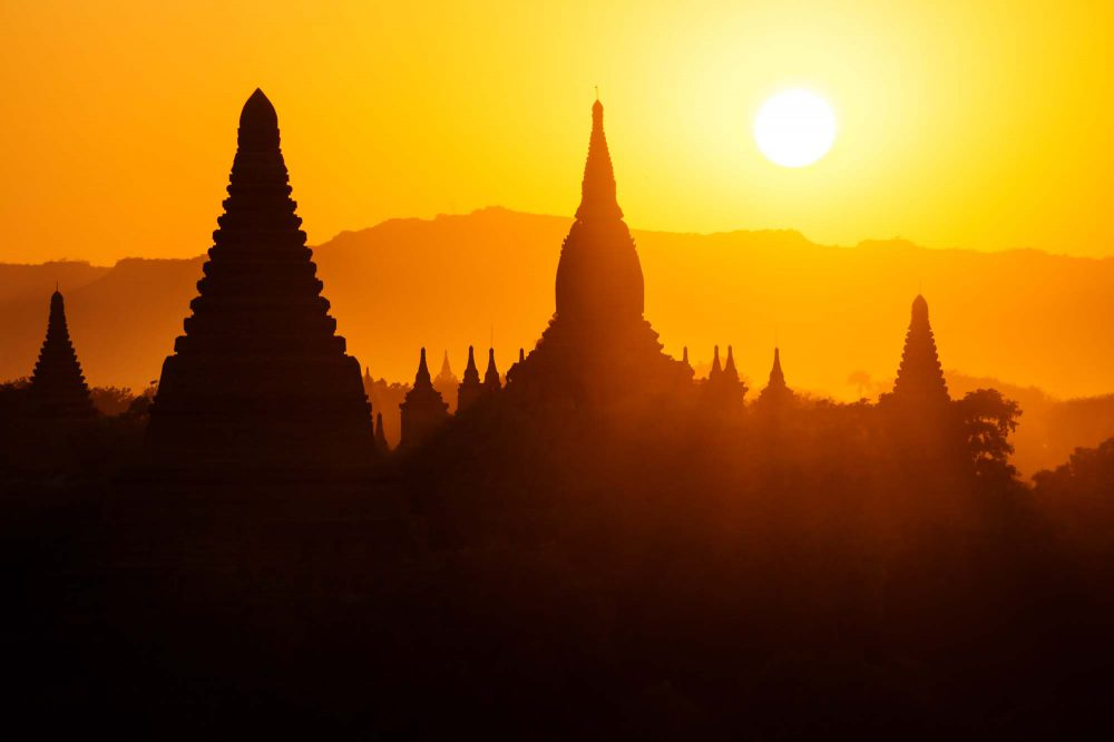 Silhouettes of Burmese Pagodas during sunset with big white sun and sunrays from the view of Shwesandaw Pagoda, Bagan, Myanmar