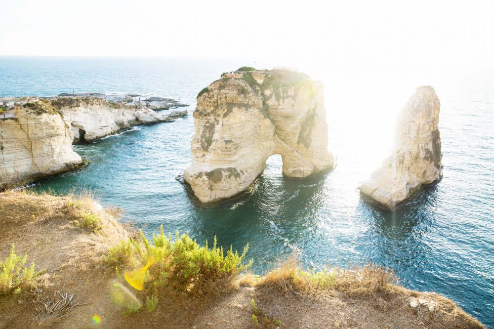 Beirut, Lebanon, Pigeon rock, arch shaped stone formations in the blue ocean along the coast