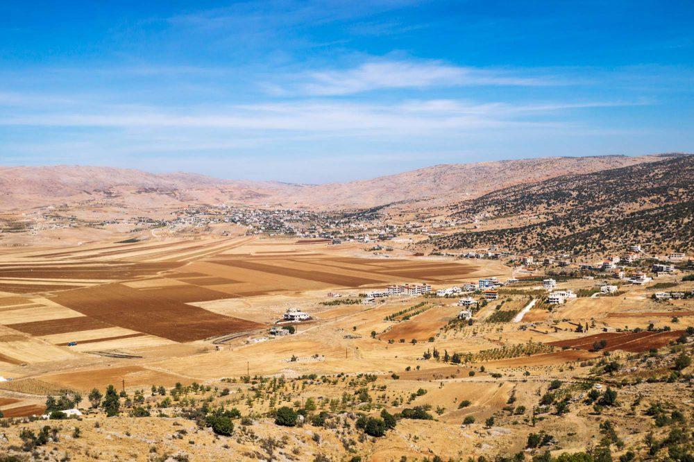 Beqaa Valley, Lebanon, Orange brown fields between the desert mountains and villages and blue sky