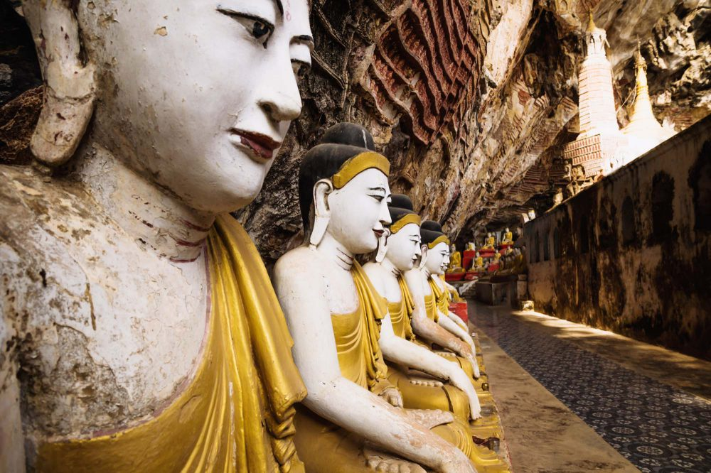 Ancient Buddha statues with golden ropes in a row under red limestone walls with Buddha carvings in Kawgun cave with a stupa, Hpa-an, Myanmar
