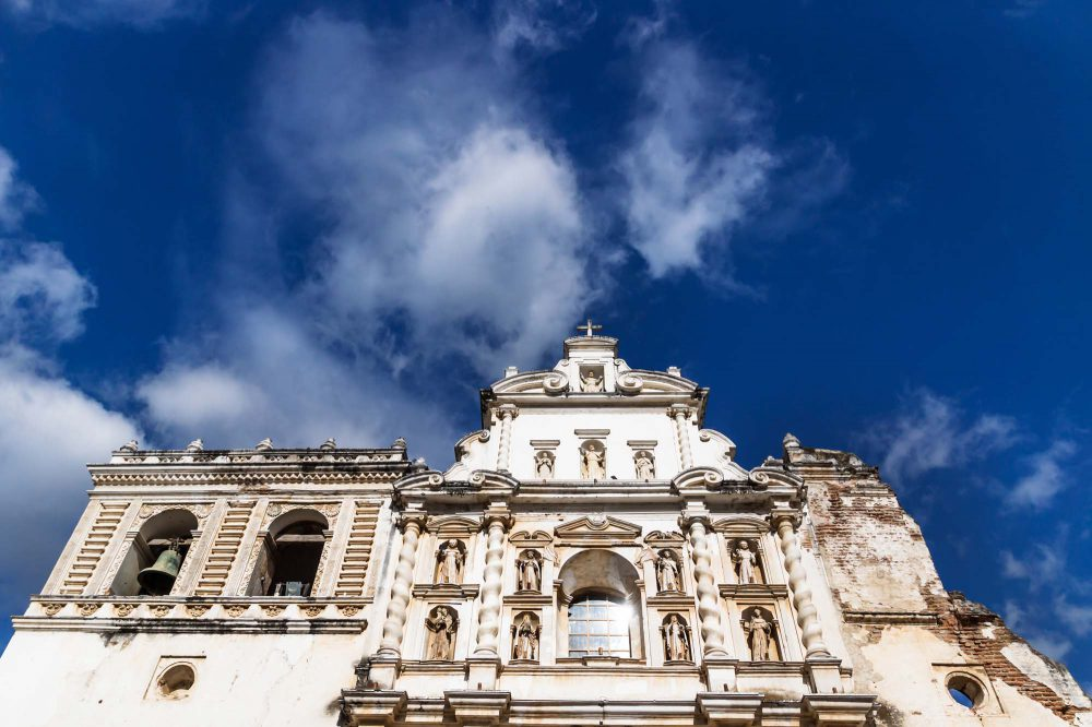 Templo de San Francisco el Grande, fassade with statues, arches, pillars, bells and cross at the top seen from low angle view with blue sky and clouds in Antigua, Guateamala, Central America