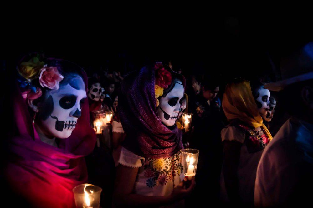 Merida Mexico Three women with Catrina costumes ad skull make-up holding candels at the parade for dia de los muertos at the Festival Des Las Animas