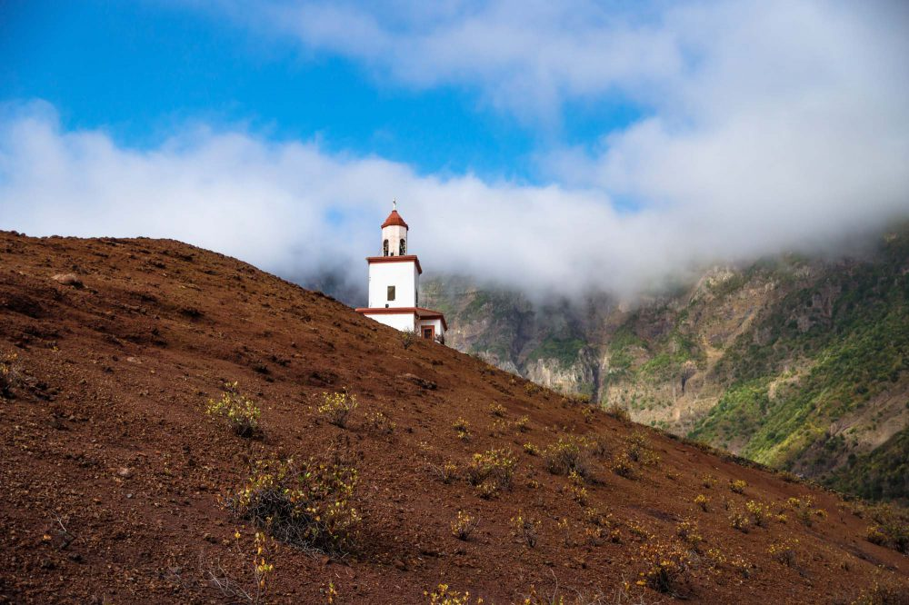 The church La Candelaria on a slooped red sand hill with green mountain cliff, big white cloud and blue sky, Frontera, El Golfo, El Hierro, Canary Islands, Spain