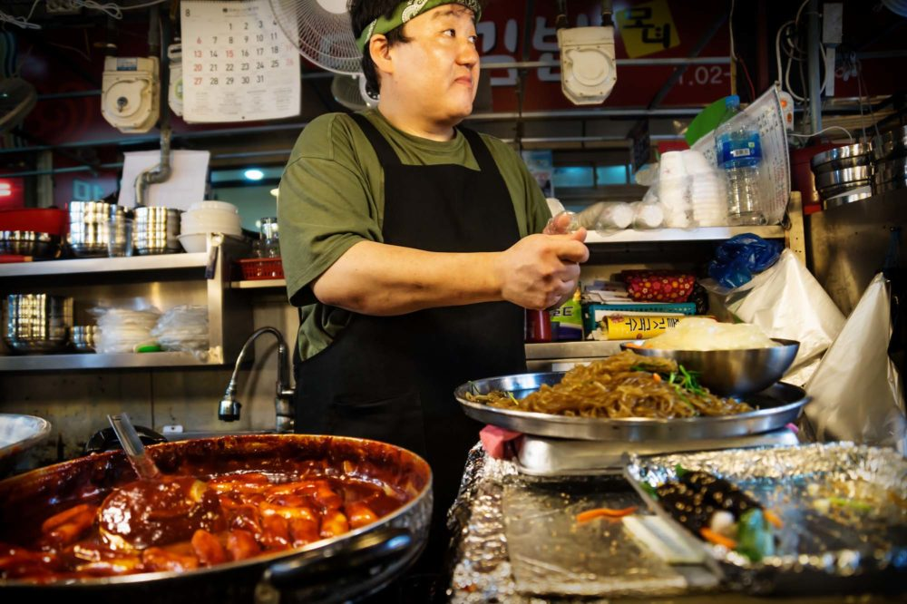 Seoul, South Korea: Cook at a street food stall with noodles and sushi in Gwanjang Market