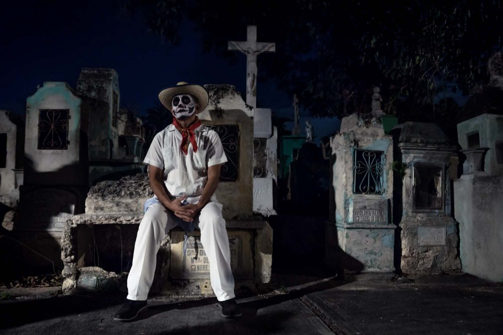 Merida Cementerio General Mexico Dia de los muertos white customed man with cowboy hat with skull make-up sitting on gravetomb surrounded by tombs at at the Festival Des Las Animas