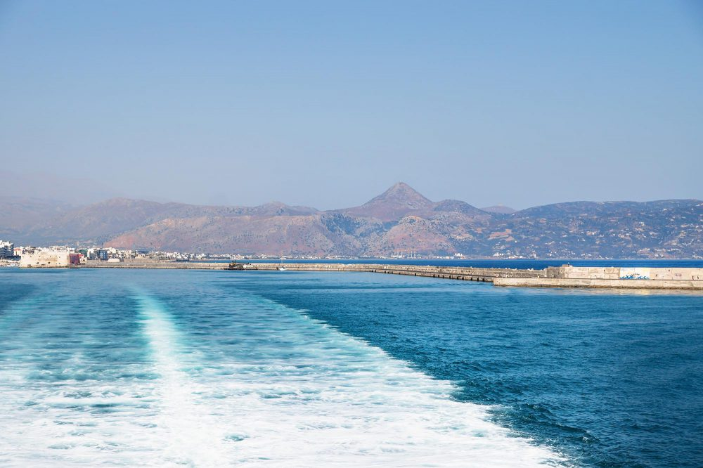 Boat trails in the ocean with view on the port of Heraklion and mountains in Crete, Greece, Europe