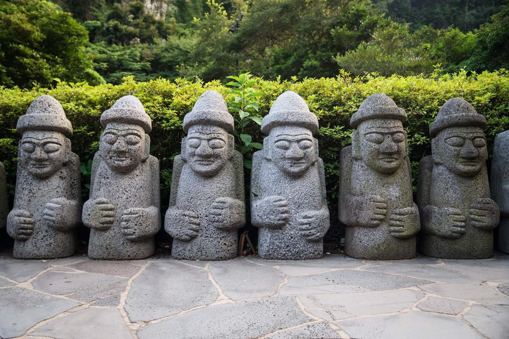 Six Dol Hareubang statues in a line in green forest, Seogwipo, Jeju Island, South Korea