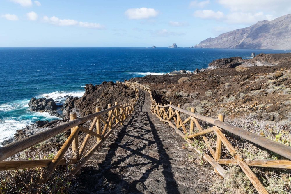 Pathway along the ocean through black lava rocks to natural pool Charco de los Sargos, El Golfo, El Hierro, Canary Islands, Spain