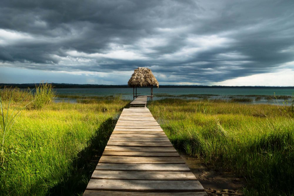 El Remate, Peten, Guatemala, Dramatic rain clouds behind hut on a dock surrounded by green reed along the lake shore with dark blue cloudscape and sunshine