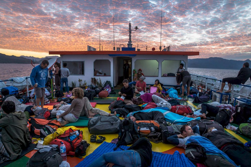 Passengers on mats and luggage on the deck of a ferry from Wakai to Gorontalo, Sulawesi, Indonesia, during sunrise with red colored clouds