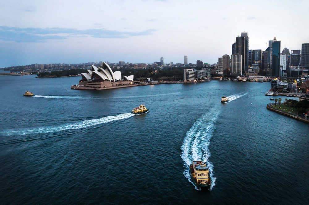 Cityscape of Sydney with Opera house and ferry boats in the blue ocean after sunset, Australia