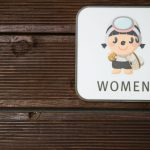 Manga comic logo of the Haenyeo woman with mask on a toilet sign on a wooden wall