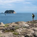 Hiker on a stone cliff with view to ocean and Moon Island, Seogwipo, Jeju Island, South Korea
