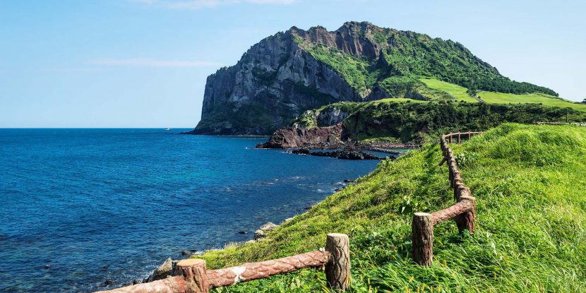 Volcano crater Ilchulbong along the ocean and the green coastline with a fence in Seongsan, Jeju Island, South Korea