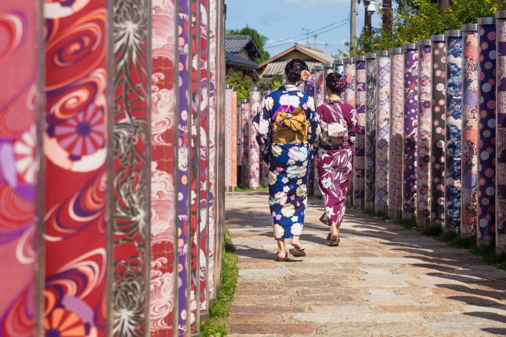 Japan Kyoto two women dressed in kimonos walk through poles with traditional colourful kimono fabrics at Arashiyama station