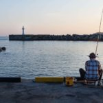 Seogwipo, Jeju Island, Back of fisherman at harbour with white lighthouse during sunset