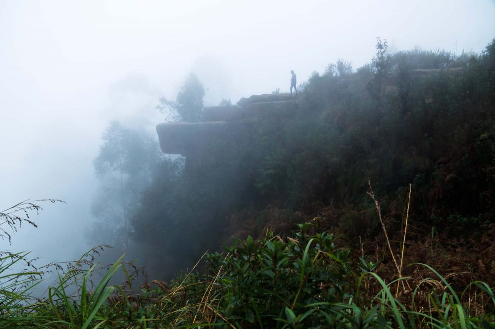 Kodaikanal, India - Man walking on rock formation called 'dolphins nose' in thick fog