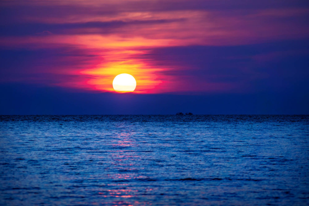 Red Purple sunset into the blue ocean with two ships in the horizont, Koh Rong Sanloem, Cambodia, Asia