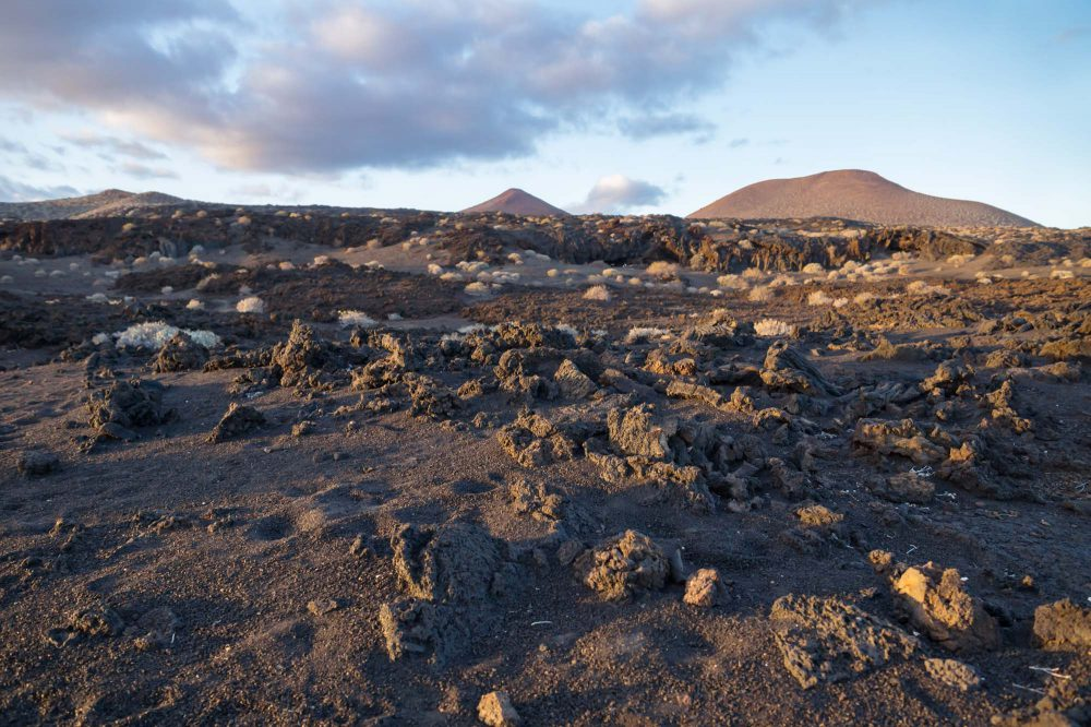 El Restinga, El Hierro, Canary Islands - Sunshined lava rocks spreaded in black sand with moon-like landscape during sunset, Spain