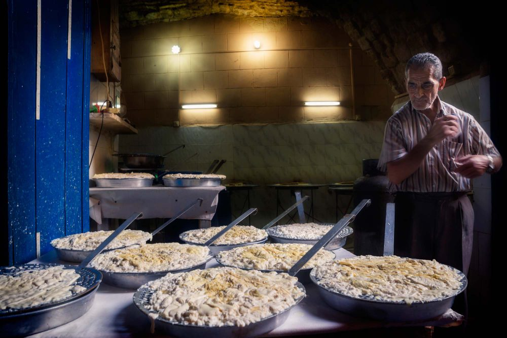 Tripoli Lebanon Cheese maker with large pans in a dark room in the souks