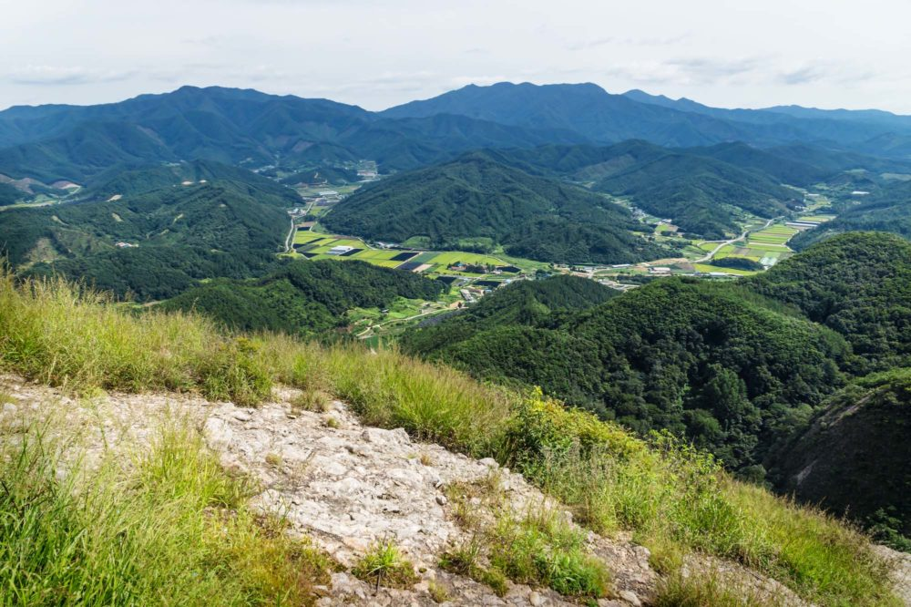 View into the valley with fields and hills from the top of Maisan mountain, horse ear mountain, Maryeong-myeon, South Korea