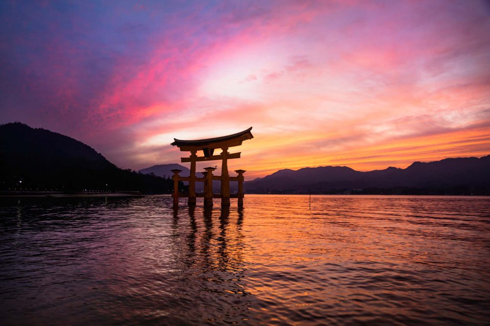 Sunset with purple, red and orange clouds and water at the Floating Torii gate in the ocean in Miyajima, Japan