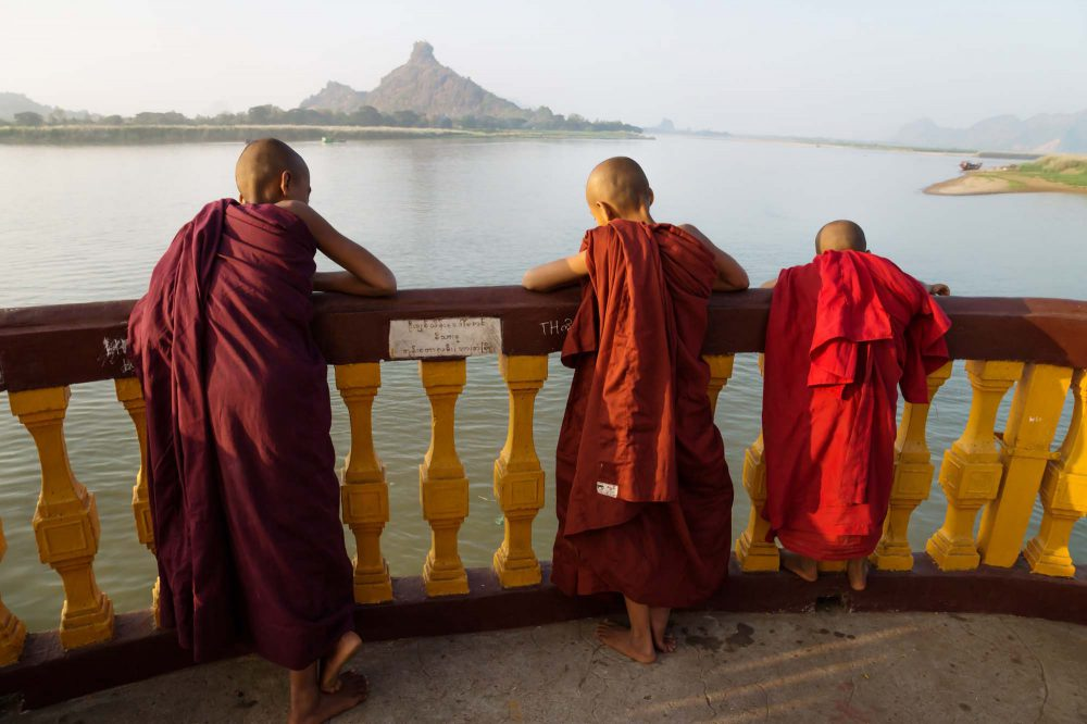 Hpa-an Myanmar Three monks standing at the pagoda along the river with mountain enjoying the sunset