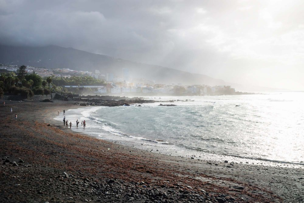 Puerto de la Cruz, Tenerife, Canary Islands, Black beach with people along the ocean with sunrays lightening the village and mountainrange, Spain