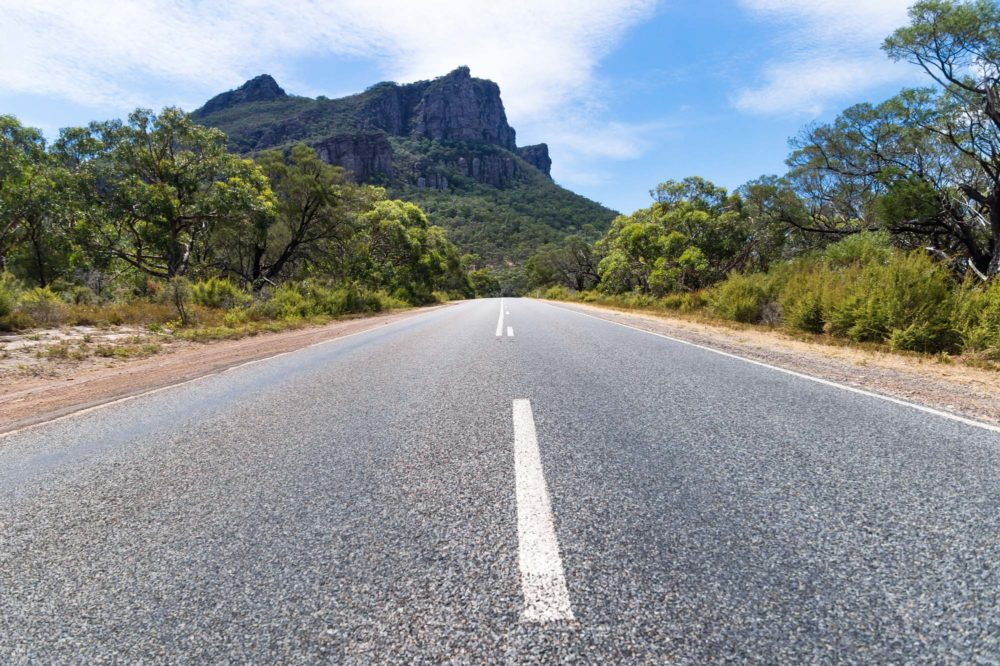 Asphalt road leading to the Grampians rocky mountains lined by trees, Victoria, Australia