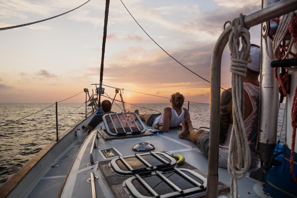 Two men and one woman sitting on the deck of a sailboat in the ocean watching the sun setting into the horizon.