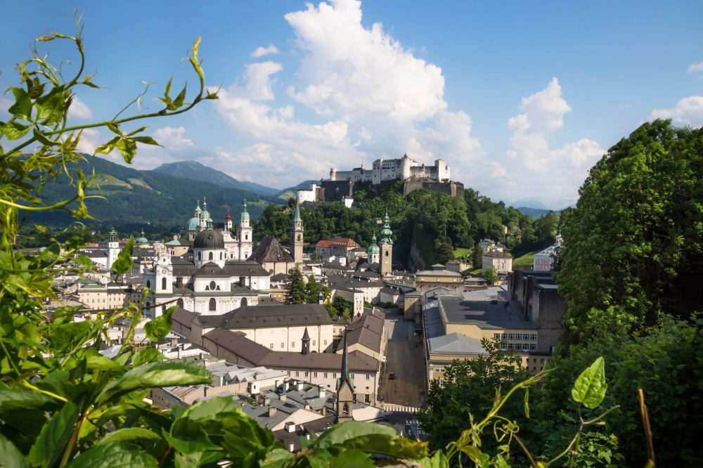 Panorama of Salzburg old town with the hills of Mönchsberg with fortress Hohensalzburg on it on a sunny day surrounded by efeu, Austria