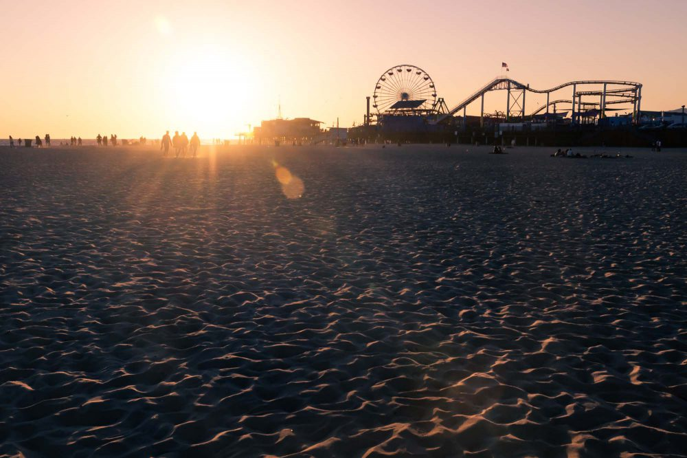 Silhouettes of people walking along Santa Monica beach and amusement park on pier with wheel and rollercoaster at sunset with lens flare, Los Angeles, California