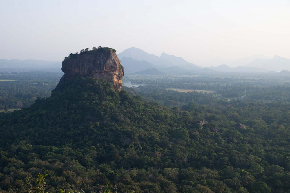 Lions Rock, red large stone formation with fortress on the top, surrounded by green forest, mountainrange and lakes in the background, Sigiriya, Sri Lanka
