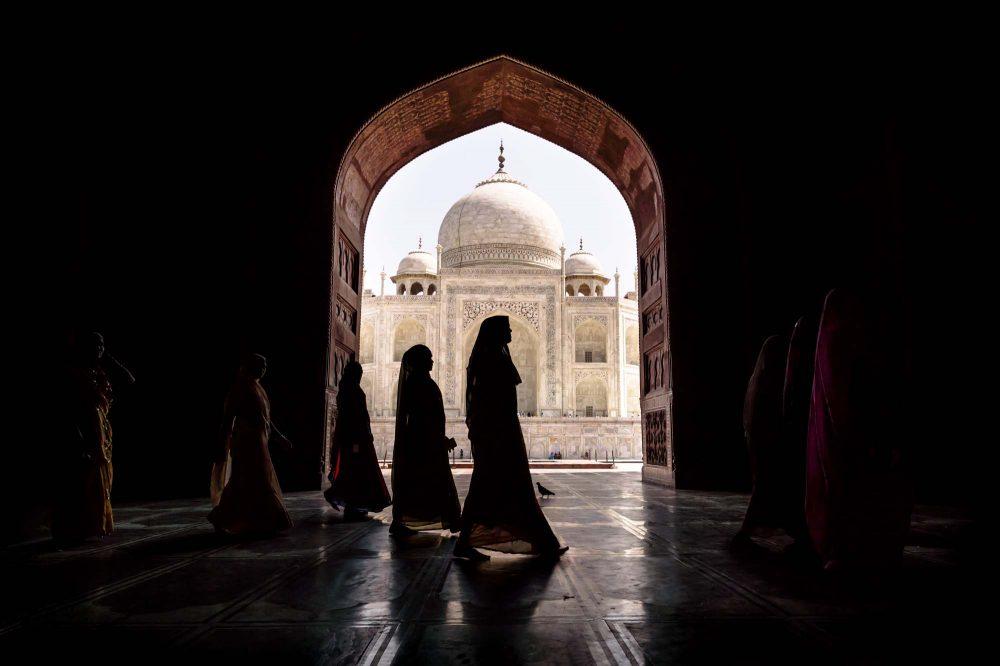 Women in traditional saris passing arch in Taj Mahal in Agra, Uttar Pradesh, India