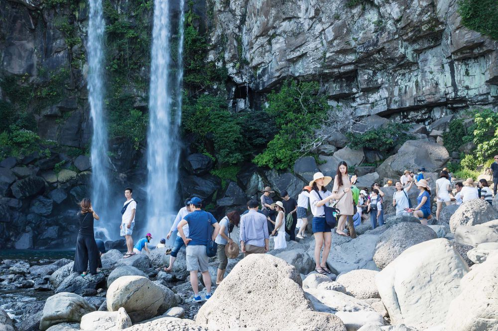 Asian tourists standing on huge stones and making pictures under the Joengbang waterfall in Jeju Island, South Korea