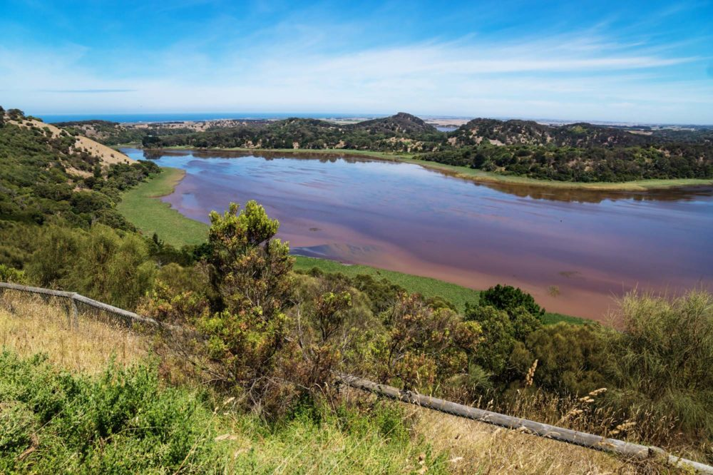 Panoramic view on red brown coloured lake surrounded by trees at Tower Hill Wildlife reserve park with view on the ocean. Victoria, Australia