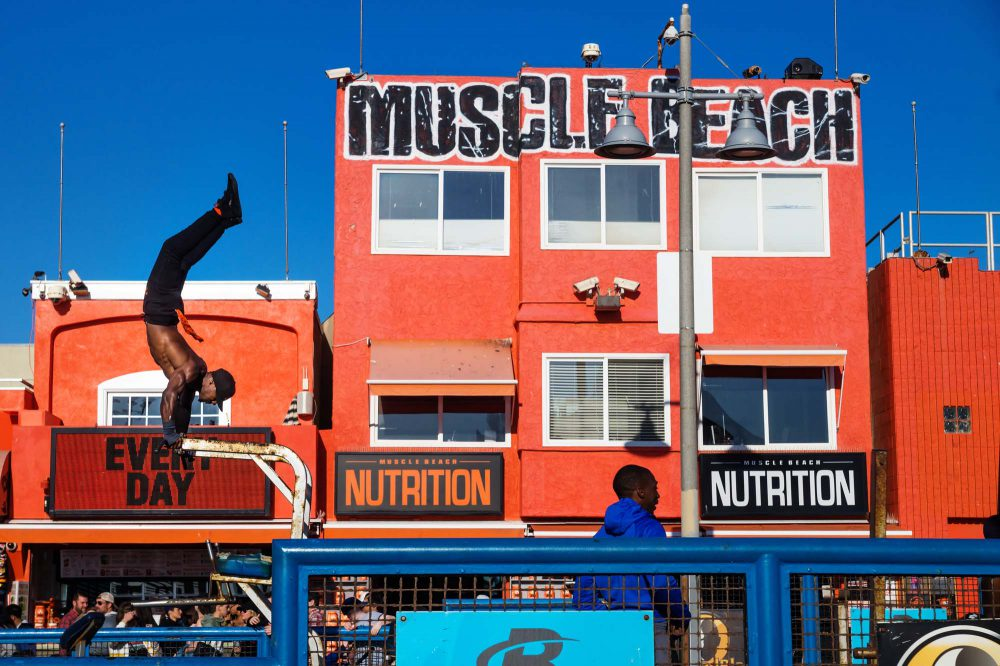 Man training figures in front of muscle beach building, Venice Beach, Los Angeles, California