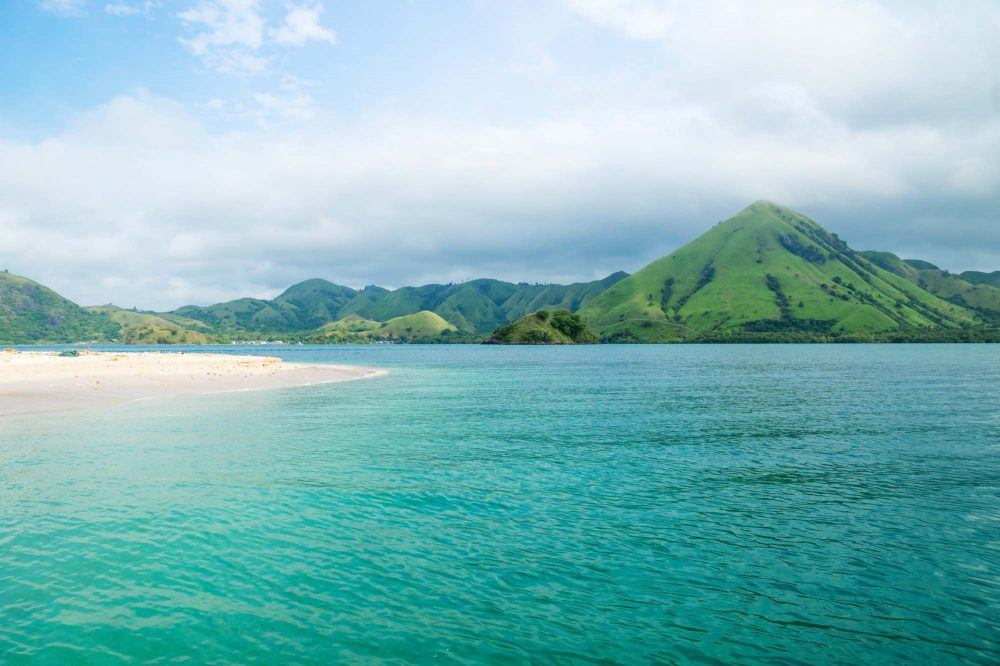 Indonesia, Volcanic mountain coastline of Flores with green hills along the turquoise ocean and sandy beac