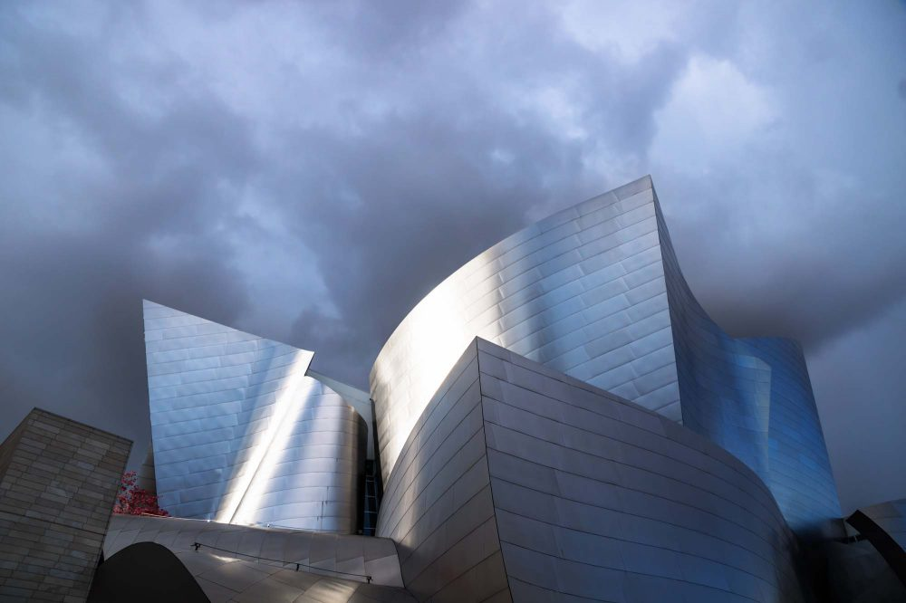 Walt Disney Concert Hall futuristic metal architecture with sunlight under dark blue rain clouds, Los Angeles, California