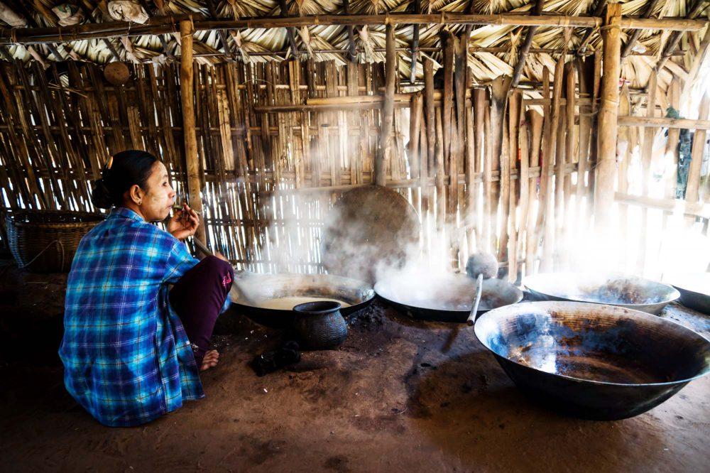 Burmese woman in Bagan Myanmar smoking cigar and cooking palm sugar in a hut