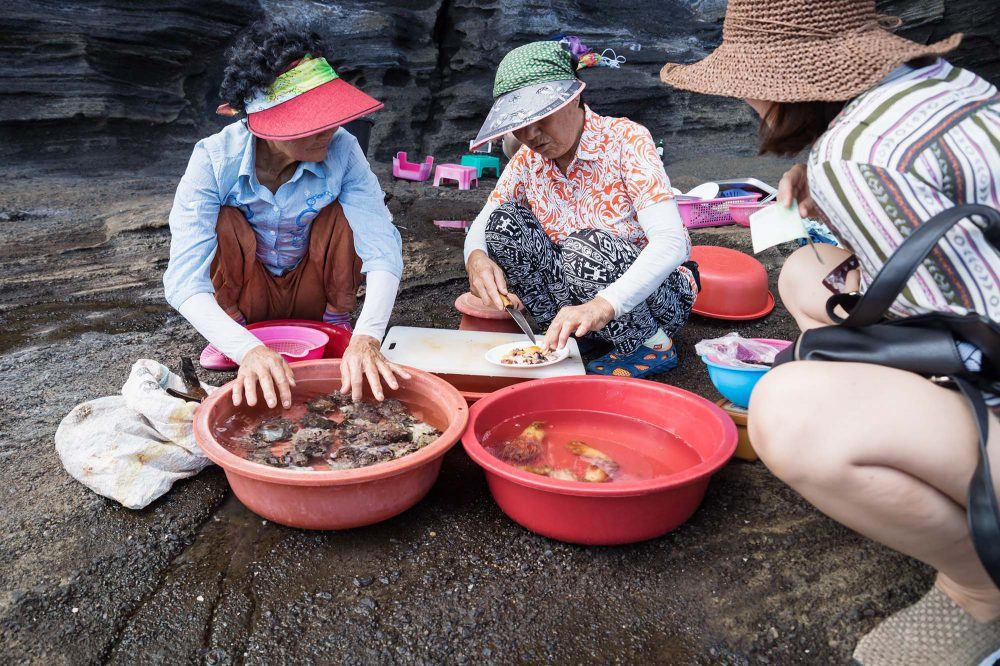 Two older women sitting on the cliff and prepare and sell fresh seafood to tourist girl in Jeju Island