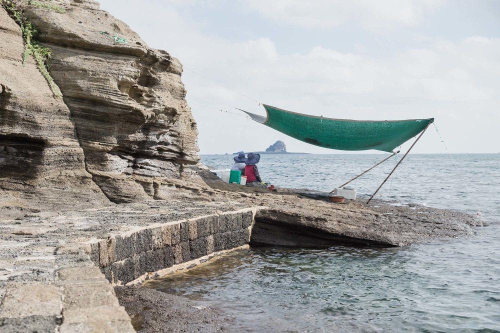 Local women selling fresh seafood sitting under a cover at the cliffs along the ocean at Yongmeori Beach, Sanbang-ro, Jeju Island, South Korea