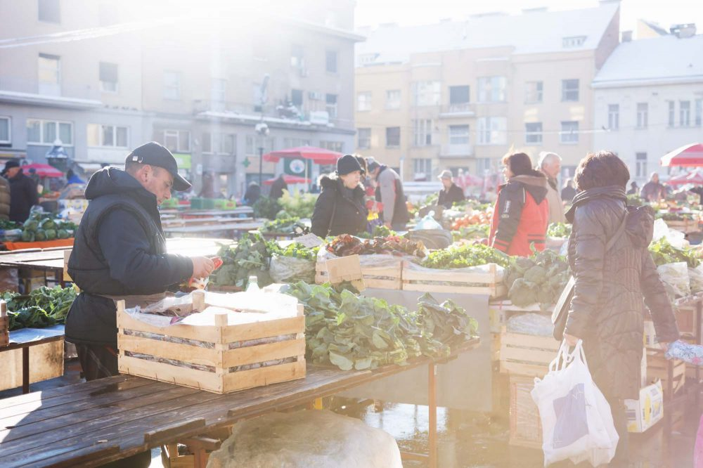 Man sorting out vegetables at Dolac market in Zagrab, Croatia during wintertime with snow at a sunny day , Croatia
